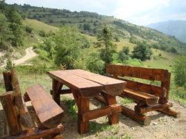 Дървени пейки и маса и гледка към съседния хълм.